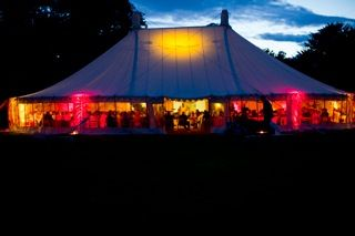 A Traditional Circular Tent by night.....This circular tent can be extended to the same footprint as the Orangery and is a great alternative for larger scale weddings and parties. Like the Traditional Canvas Pole Tents, it is made from a 12oz waxed cotton canvas in a cream colour and has our signature burgundy piping along a scalloped exterior valance.