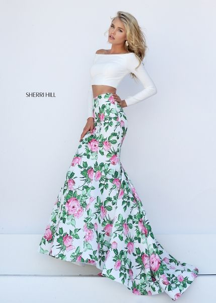 Brands like Sherri Hill are giving prom dresses an interesting twist with floral, casual patterns. This rose-patterned skirt is paired with a form-fitting, long sleeve, white crop top. Two simple pieces come together for a different spring look for prom 2016. Look for nude or matching pink heels for this gown.  You can wear almost any earring you choose. It can be as big as you like, but try to keep the shape simple (maybe a round shape).