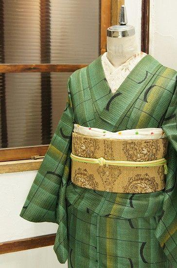 深みのある緑のグラデーション美しいストライプに、ミッドセンチュリーモダンデザインを思わせる曲線と直線が調和したジオメトリックパターンが織り出されたスタイリッシュなウールの単着物です。
