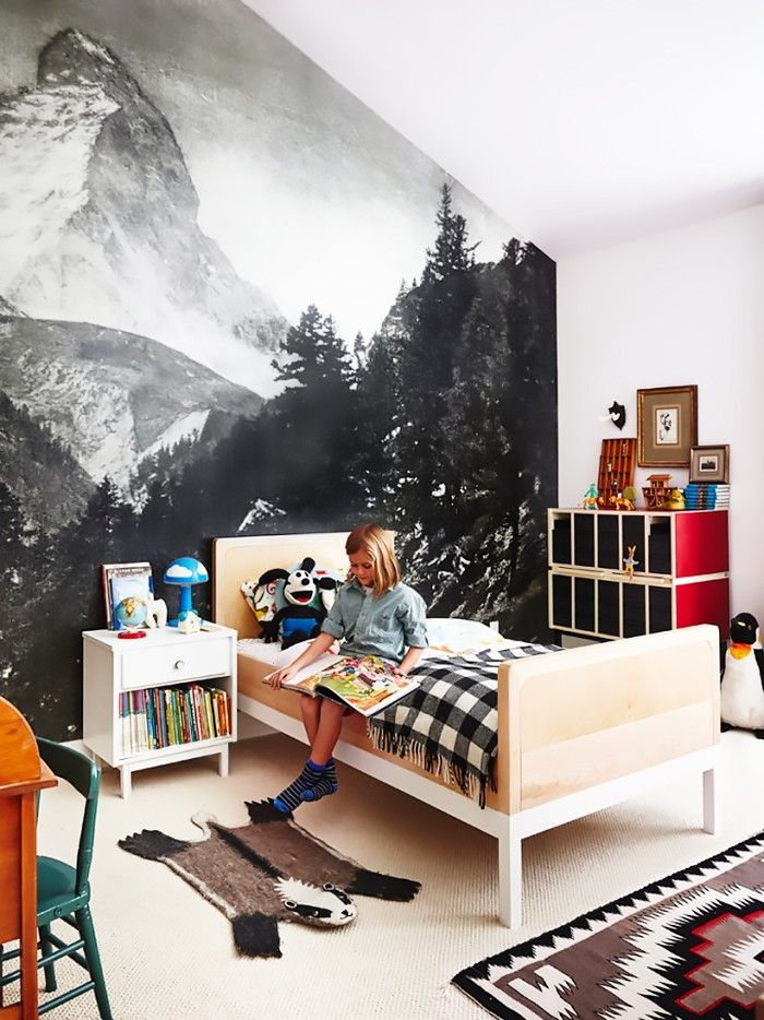 This eclectic kids room is the stuff of interior design dreams with midcentury inspired furniture, a plaid lumberjack blanket, a navajo rug and a super cool mountain mural.