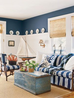 """Blue and White Study~In office-study, Ralph Lauren Home outdoor fabric on chair cushions and sleeper sofa. Plates above wainscoting, chest as table and nautical wall lamp, all antiques. """"Steamed"""" hand-hooked wool pillow by Chandler 4 Corners. Coral-design linen pillow by Thomas Paul. Nickel lanterns and sisal rug, all from Restoration Hardware. Horizons shades."""