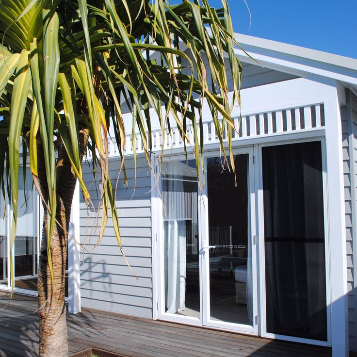 Pandanus tree against Linea board exterior. Glass doors and fretwork between posts.  @the_beach_lounge