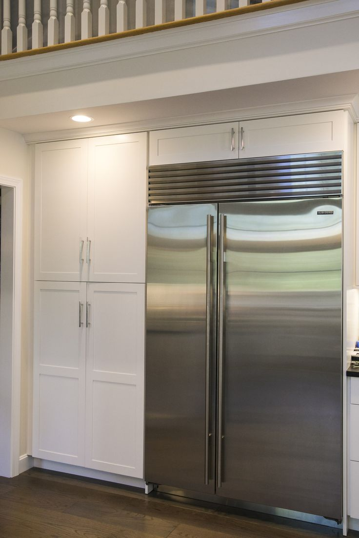 White Shaker cabinets with modern brushed nickel finishes custom built around subzero refrigerator.