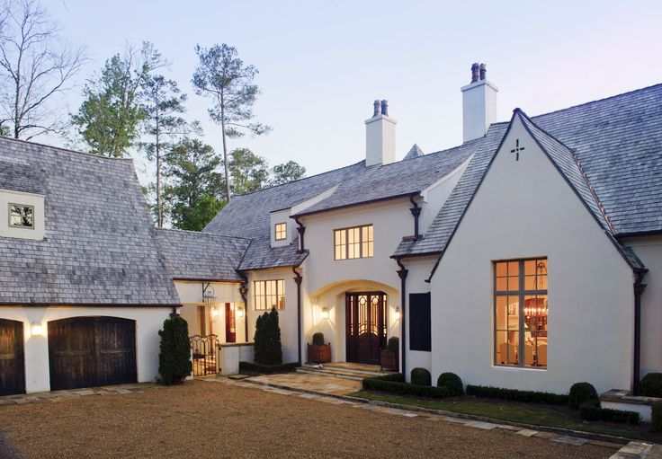 Love the stucco, windows, and carriage doors. Looks modern french country.