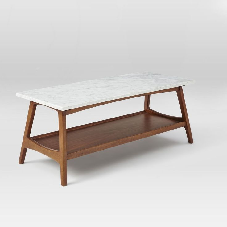 """Top this. Our Reeve Mid-Century Rectangular Coffee Table's tailored lines and storage shelf make it a great small-space solution while its marble top gives it a luxe, finished look. 48""""w x 20""""d x 17""""h. Marble top. Solid wood base with Pecan finish. Imported. Online/catalog only."""