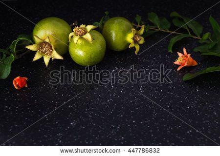 Green pomegranate closeup decorative background, dark photography.