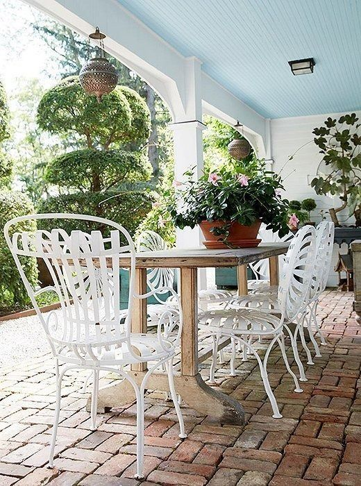 Incorporate the same vignettes you have indoors into your outside spaces. You can start by transforming your covered patio into a highly functional spot with two distinct zones: one for alfresco dining and one for displaying your curated mix of plants, flowers, and tailored topiaries.