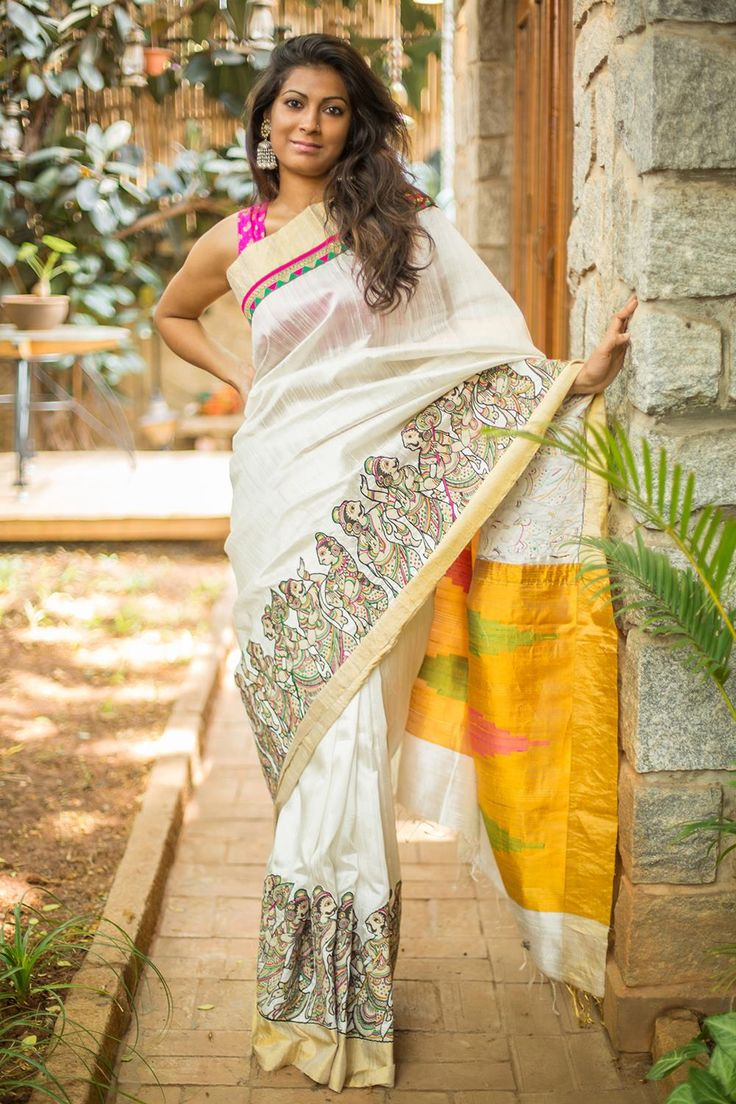 Bringing you another stellar raw silk drape to expand your choices! A rich sheen white saree with handprinted folkloric images in Kalamkari appliqued into the border and a striking mustard yellow pallu with pink green temple motifs. Be the stand out girl this wedding season in this special number.Pair with a rich mustard yellow blouse in keeping with the pallu. Or don a pink, green or even a subtle gold blouse to spin your own magic. #kalamkari #saree #India #blouse #houseofblouse