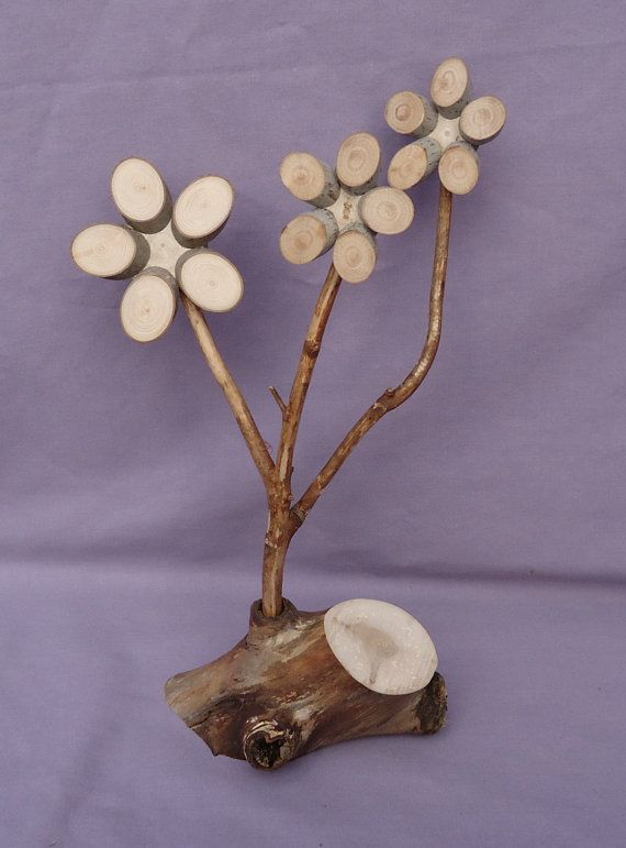 "These ""winter flowers"" are not only hearty but extremely easy to care for! Each unique piece is crafted from aged and naturally weathered maple. The wood has been completely dried and STERILIZED but nothing has been applied so it retains all its natural beauty. The ""flower stems"" fit into sockets in the base so you can turn them as you like. Display as is or add some seasonal trimming and they'll get a smile in any season. And yes, they adapt perfectly to MAN CAVE conditions! (Remember…"