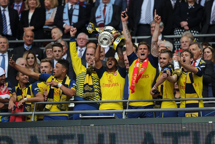 Arsenal's Theo Walcott lifts the FA Cup after the FA Cup Final between Aston Villa and Arsenal at Wembley Stadium on May 30, 2015.