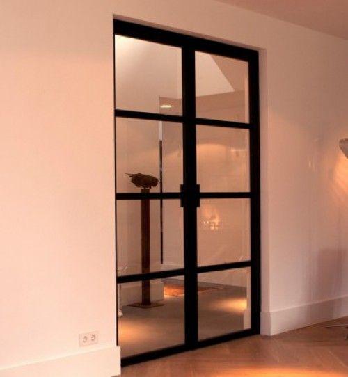 Houten vloer i.c.m. zwarte stalen deuren en wit.
