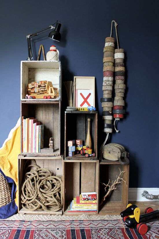 For #toy and #book-storage, we created this stacked arrangement of vintage wooden crates. We nailed each of the crates to each other and then secured to them wall. I then filled the crates with a selection of sea-faring treasures, favorite toys and books. On the wall, is a string of old #cork-buoys