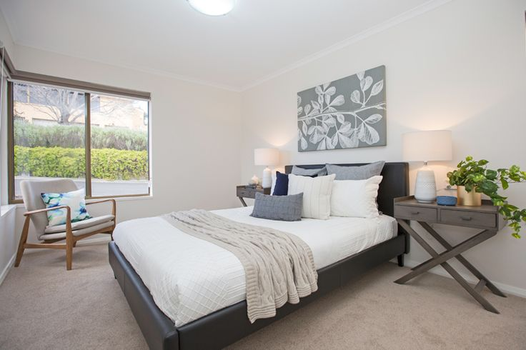 Master bedroom, black leather bed frame, timber cross leg side tables, white linen, blue velvet cushion