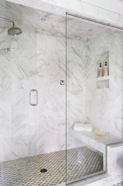 Calacatta Gold marble and Walker Zanger mosaic tiles line the walk-in steam shower outfitted with both a rainhead and hand shower. Dream Shower! - Traditional Home ®/ Photo: Werner Straube / Design: Rosemary Merrill