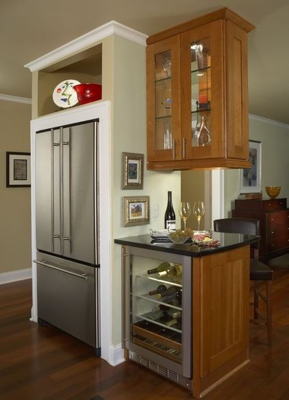 This is particularly nicely done. The very linear refrigerator fits neatly into the opening and is trimmed out with house molding. The display shelf above draws the eye up. With a wine refrigerator next to the main refrigerator in a small peninsula cabinet, this is a good area for dispensing drinks.