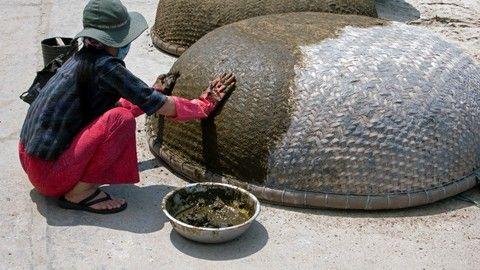 Woman seals traditional circular woven coracle boats Cham Island off historic Hoi An Vietnam