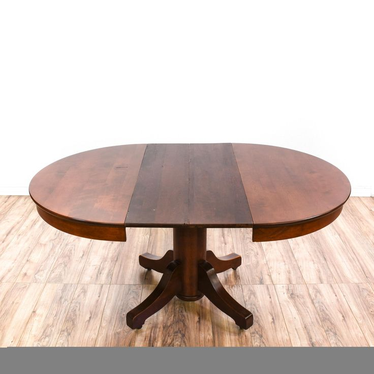 This traditional dining table is featured in a solid wood with a mahogany finish. This vintage wooden table has two extendable leaves, a quadrangular base, and oval table top. Perfect for formal or casual dining! #americantraditional #tables #diningtable #sandiegovintage #vintagefurniture