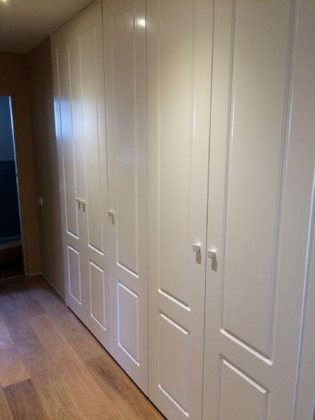 Armario empotrado de puertas abatibles pantografiadas en lacado blanco.