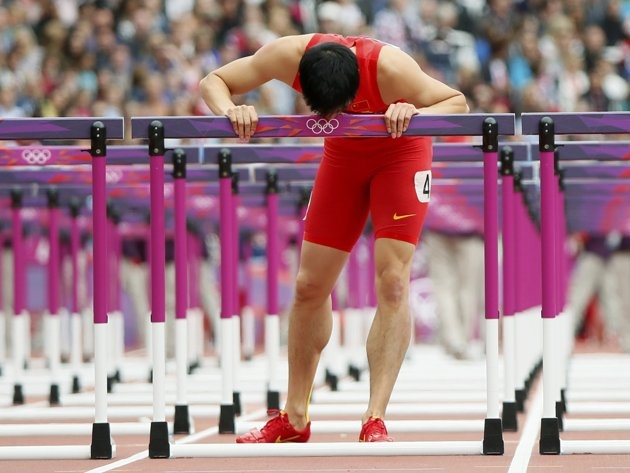 China's Liu Xiang kisses the last hurdle in his lane during his men's 110m hurdles round 1 heat at the London 2012 Olympic Games at the Olympic Stadium