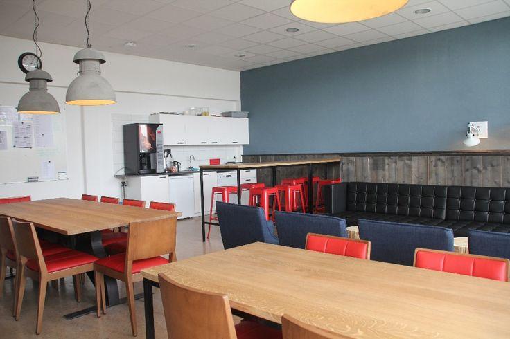 Personeelskamer Tender College IJmuiden - keuken met bartafel van massief vintage eiken blad en stalen onderstel, rode metalen barkrukken, staalblauwe wand en donkergrijs gebeitste lambrisering van steigerhout.