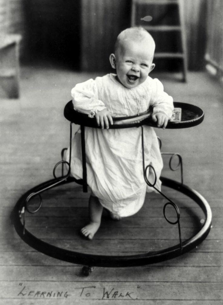 A joyful baby takes a spin in a walker in 1905.