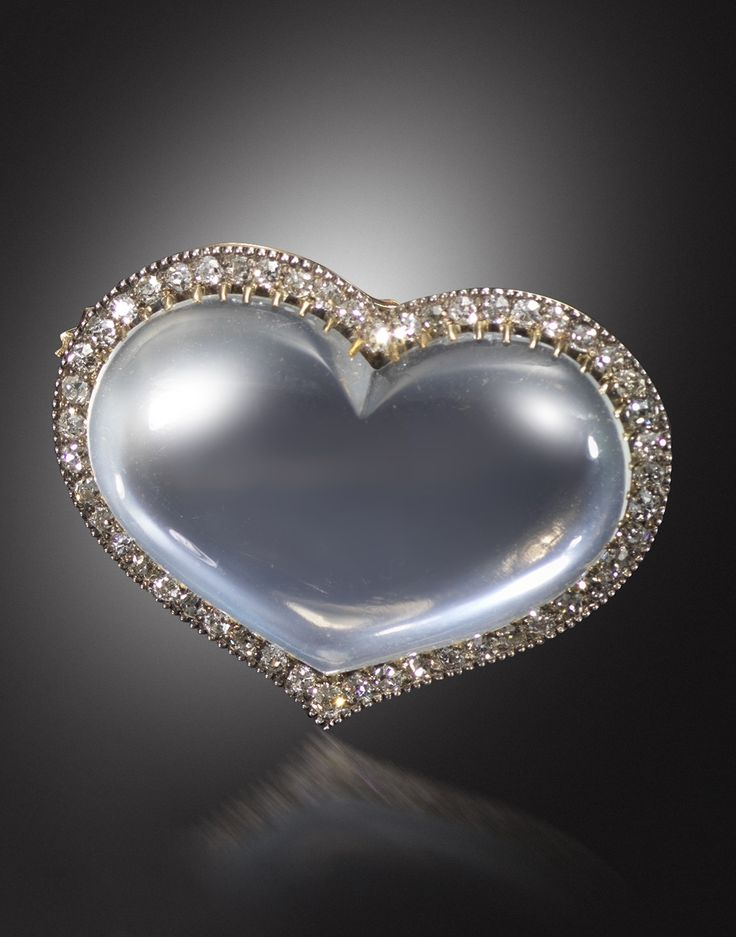 A Victorian moonstone and diamond brooch, the heart-shaped moonstone cabochon is set within a surround of cushion-shaped diamonds in silver and gold, detachable brooch fitting to reverse, 3cm wide.