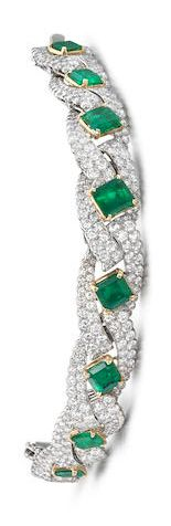 A fine emerald and diamond bracelet, by Cartier, circa 1960 The articulated bracelet set with eight graduated step-cut emeralds, each between courses of brilliant-cut diamonds, diamonds approximately 11.50 carats total, signed Cartier Paris, numbered, length 16.0cm