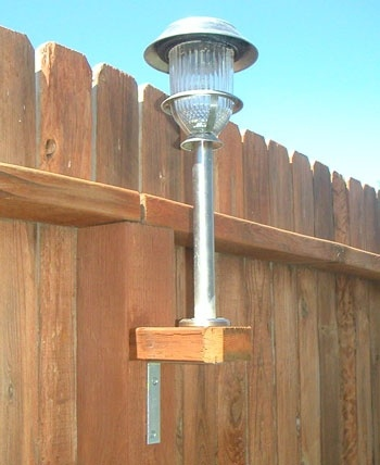 Great idea for a large back yard: Use your solar lights. They arent just for the ground!  Take a 2x4 and cut them into squares to fit the existing fence posts. Using galvanized screws - not nails - to screw a L bracket to the underneath base. Then on top, screw on the stake.