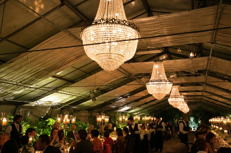 Warm atmosphere for the wedding reception in the greenhouse lighted by crystal chandeliers.
