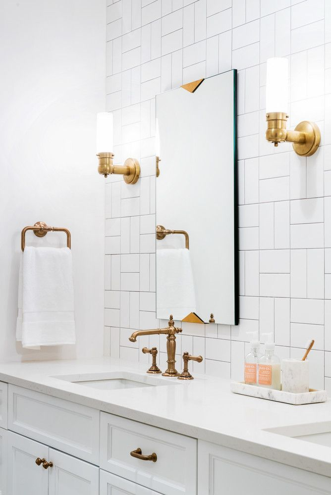 White vanity - double vanity - marble tops - white patterned subway tile - brass fixtures - brass hardware - two mirrors