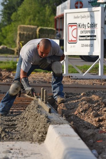 Jaime Quinonis builds up the curb on one of the slabs at the Bairds Express Car Wash located between Prudential Real Estate and F Bank.