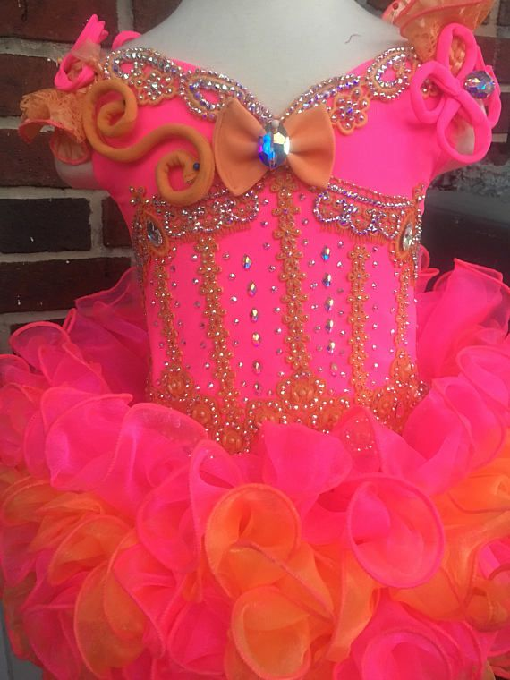 Medium Glitz pageant dress. Glitzed with Swarovski crystals Size 3/5. Includes hair bow, bustle bow and bloomers. Bright Azalea and Mango colored fabrics.