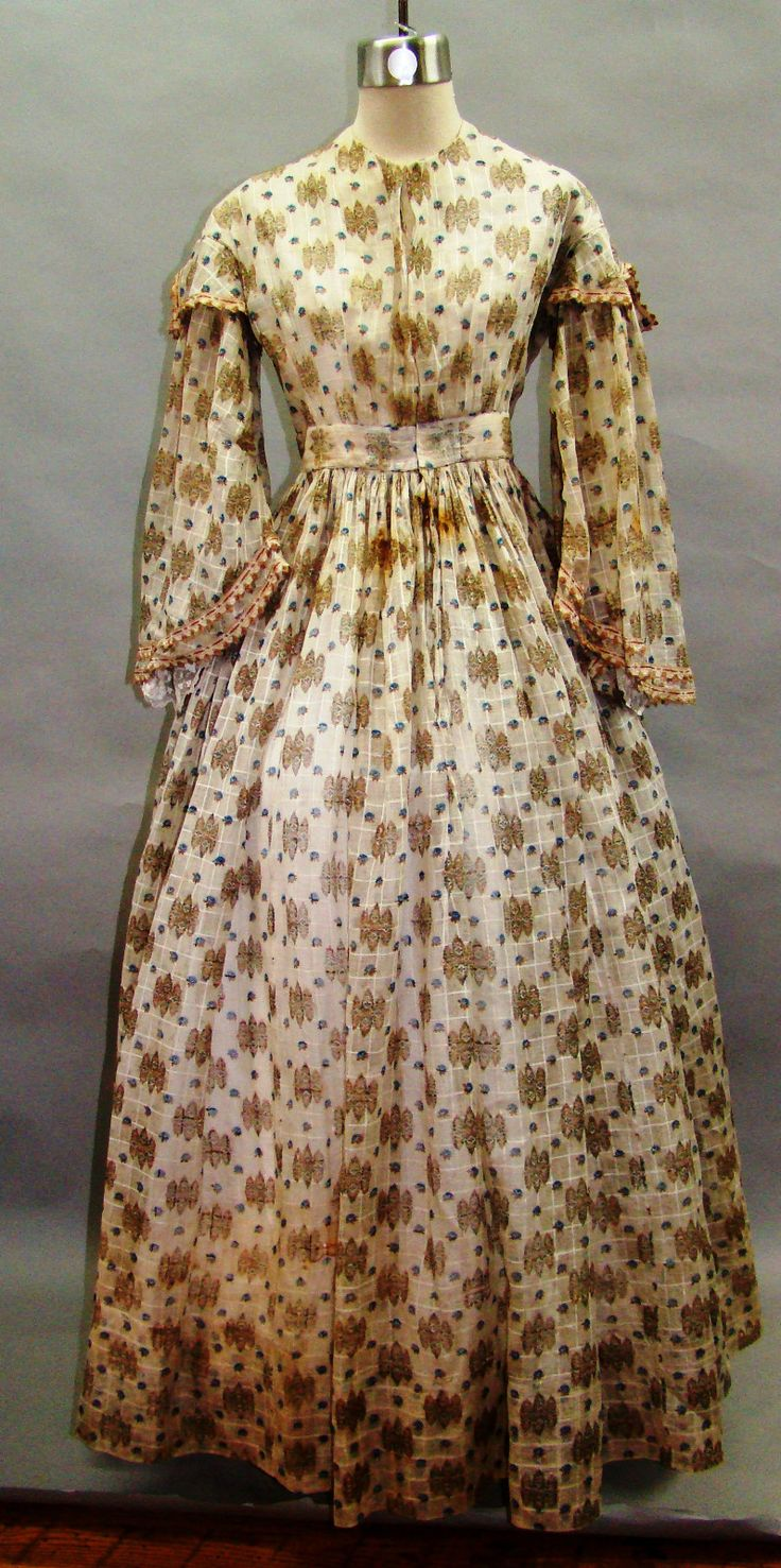 "All The Pretty Dresses: Mid 1860's Sheer Dress Light & airy sheer dress. Pagoda sleeves have little notched sleeve caps & trimmed in silk floral & fringed ribbon. Ribbon incredibly detailed for it's size - only 1/2"" wide, not counting the fringe at the bottom. Bodice entirely lined wt muslin & darts boned wt what appears to be baleen. Fabric is printed windowpane light muslin. Sleeves still have undersleeves attached at shoulders. Bodice closes wt hooks & eyes. Approx 31"" B, 25"" W, skirt L…"