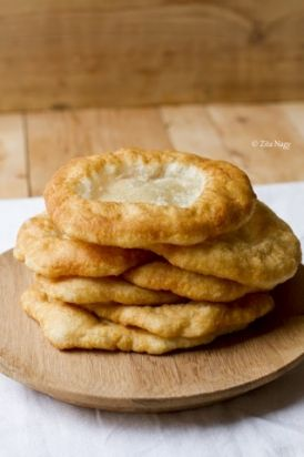 Lángos - Hungarian Fried Bread  - A plate-sized sheet of fried dough that is usually smothered with sour cream and cheese. Other possible toppings include garlic sauce or ketchup.