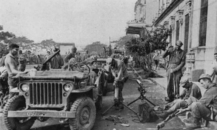 1st Cavalry Division cleaning weapons shortly after the liberation of Allied POWS at University of Santo Tomas, Manila, Philippine Islands. February 1945