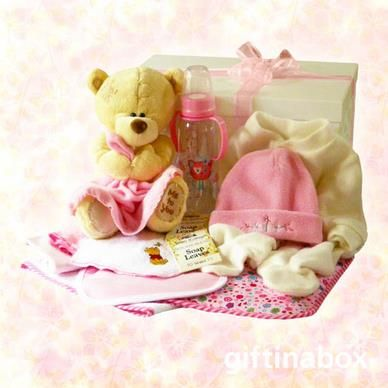"""Welcome to the new baby girl of the family. Give her lots of love with these beautiful products and her first """"me to you"""" hug blanket teddy bear. All goods are lovingly presented in a large, white gift hamper box decorated with pink ribbons and tissue paper.   """"Me to You"""" hug blanket teddy bear Hooded towel Full baby grow Baby beanie baby bib 2 x facecloths Baby bottle Baby waterproofs Sachet of bath soap leaves for mom"""