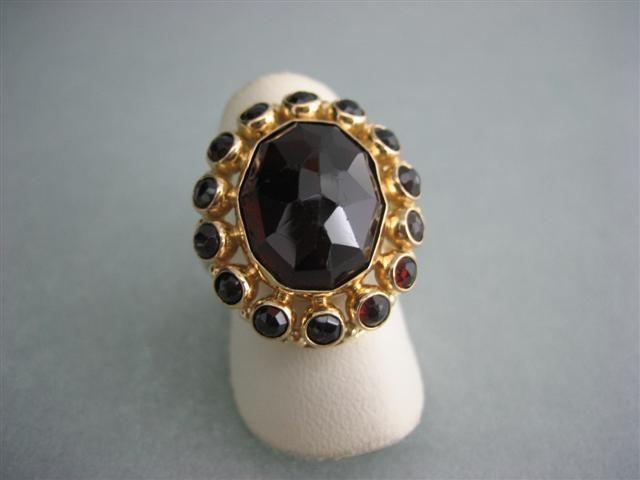 Ring van goud met granaat en kleine granaat steentjes rond om
