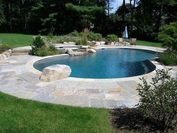 outdoor swimming pool kidney shaped pool natural stone spa area lawn