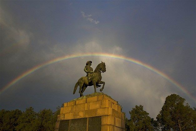 Resim: A rainbow forms over the statue of Louis Botha, the first Prime Minister of the Union of South Africa, at Union Buildings in Pretoria, South Africa. (© Matt Dunham/AP)