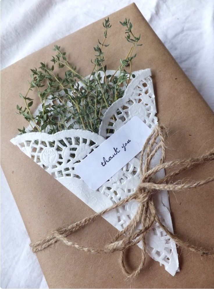 Simple but charming gift wrapping idea. Wrap item with brown craft paper, make a tag using fresh springs for Rosemary wrapped in a paper doily and finish with jute twine.