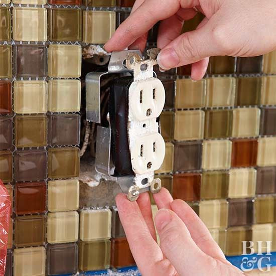Switch off the power at the breaker panel, unfasten the two screws holding the switch or receptacle, and gently pull it away from the wall. When tiling and grouting are complete, add a box extender as shown. Because of the extra thickness of the tile, you might need longer screws.
