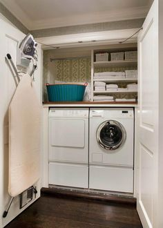 Double closet doors open to reveal a small and efficient laundry room filled with a Miele washer and dryer tucked under a small shelves, with backs of shelves lined with wallpaper, alongside an iron and folding ironing board lining one of the closet doors.