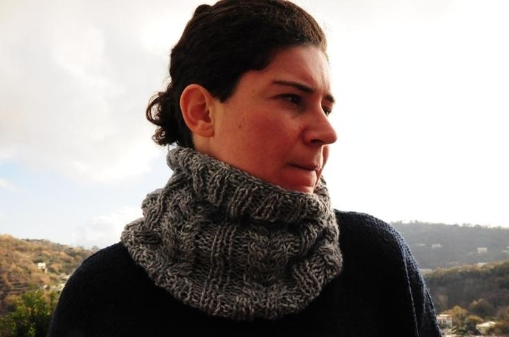 Scaldacollo grigio lavorato a maglia e con trecce.