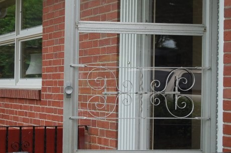 Most homes had a glass/screen door like this. Many had the initial of their last name on the metal decor in the middle of the door.