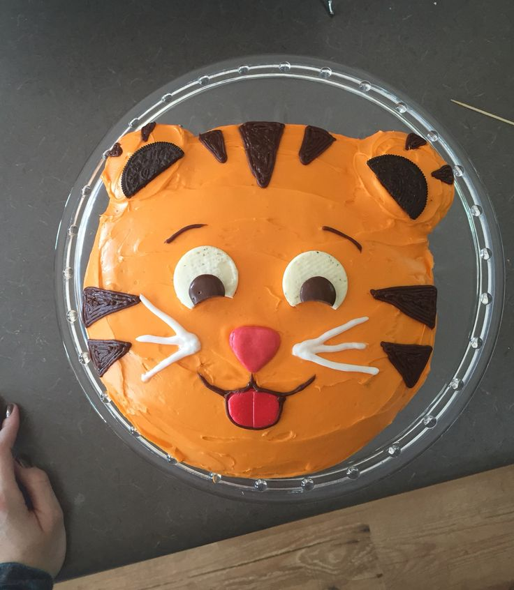 Daniel Tiger Cake. Starburst nose, airhead tongue, white gel frosting for whiskers, chocolate frosting piped for stripes and eyebrows, Oreo filling for whites of eyes, Hersey drops for pupils, Oreo cookie for ears