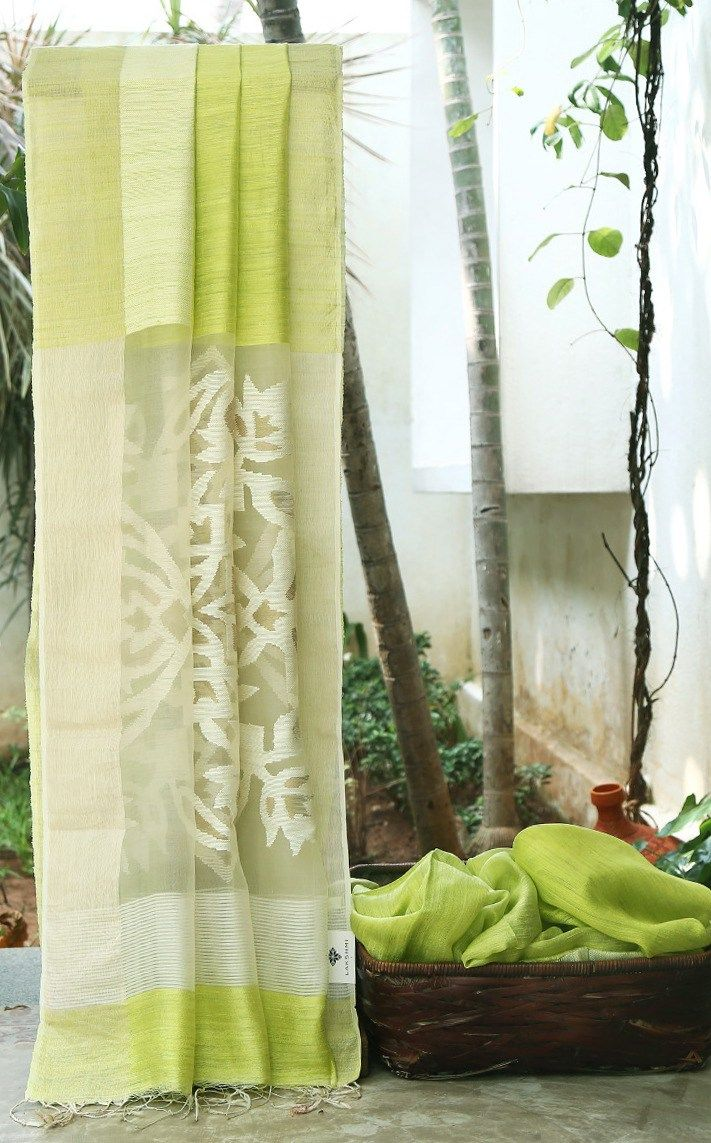 CHARMING LIME GREEN MATKA SILK IS COMPLEMENTED BY KORA PALLU WITH INTRICATE…