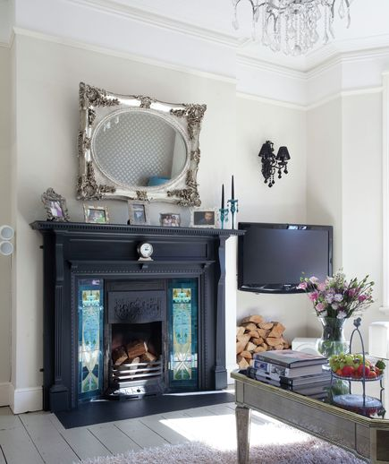 Mix It Up Formality meets functionality in this unique living room, which is tight on square inches. Hanging an ornate mirror above the fireplace is a wise decorative decision and also opens up the room making it feel larger. A TV mounted in the corner is subtle and smart (Hello, family movie nights by the fire!)