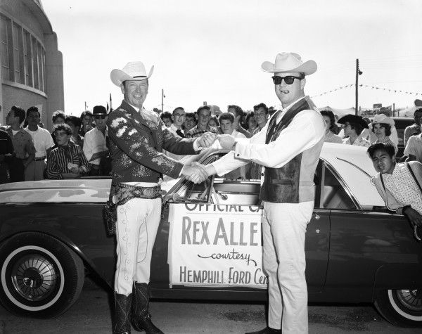 Red McCombs (right), president of Hemphill Ford, presents singing cowboy Rex Allen with keys to a Thunderbird for use as his official car during his appearances at the San Antonio Livestock Show and Rodeo, February 1962. (MS 355: Z-0751-E-01)