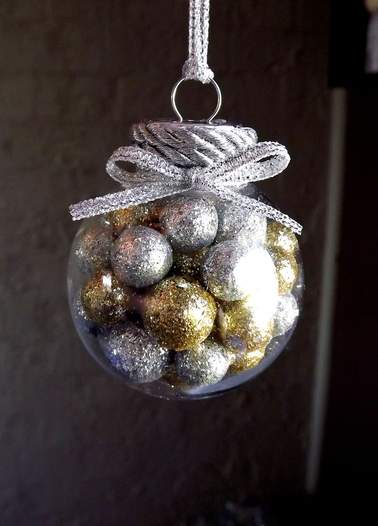 Christmas decoration filled with mini gold and silver polystyrene glitter balls; finished off with silver twine and silver ribbon bow. Plastic fillable bauble