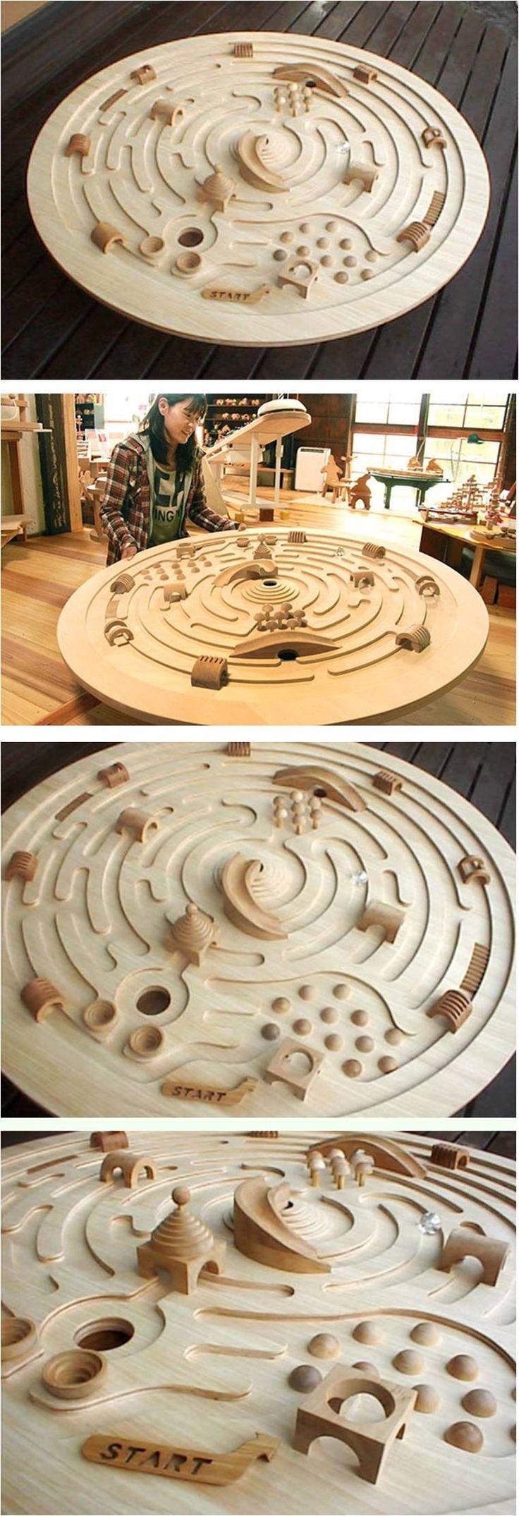 Großes schwenkbares Holzlabyrinth von Ginga Kobo Toys, Japan – Ein immenses Raumschifflabyrinth mit einem Durchmesser von 120 cm. Die Murmel 3 cm. Große Glaskugeln rollen um die Mitte herum. Zielen Sie auf die Rutsche, die in die Mündung des Vulkans führt! Kreative Hindernisse blockieren den Weg! Ideal, um kooperatives Spiel zu fördern, da 2 oder 3 Kinder zusammenarbeiten können, um das Labyrinth zu erobern.